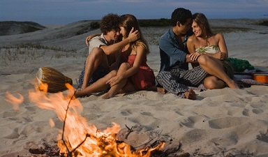 Two Couples Sitting Around Campfire at Beach --- Image by © Sean De Burca/Corbis